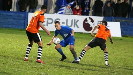 South Normanton's Eric Graves works his way between defenders Jordan King and Simon Lappin.