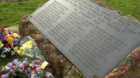 Floral tributes beside the memorial recording the Hunstanton victims of the 1953 flood disaster.