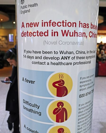 A Public Health Engalnd poster showing the symptoms of coronavirus at the arrivals concourse at Heat