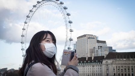 A woman wearing a face mask takes a photo on her phone from Westminster Bridge in London. James says