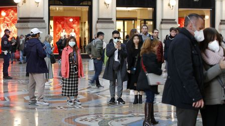 Tourists wearing masks walk in Milan. Italy has seen a number of cases as the virus spreads to Europ