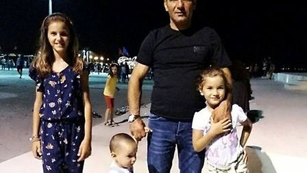 Mr Ismaili at home in Albania with his three children. Picture courtesy of the Ismaili family.