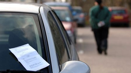A penalty charge notice is placed on a car windscreen by a Norwich City Council parking attendant. P