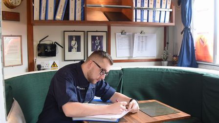 Commanding officer, Lt. Matthew Smith, in the ward room of the Royal Navy patrol boat, HMS Biter, mo