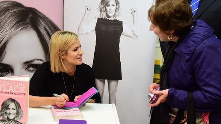 Caroline Flack signing her autobiography Storm in a C Cup at an event in Norwich in 2015, with fan V