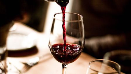 Red wine being poured into a stem glass at the table. Photo: Getty Images/debyaho/iStockphoto