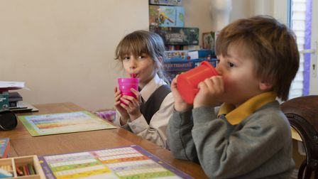 Emily (left), 9, and Benjamin (right),3, have their milk, at home on the first day of home schooling