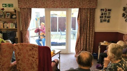 Andy performs for residents behind glass doors. PHOTO: Park House Care Home