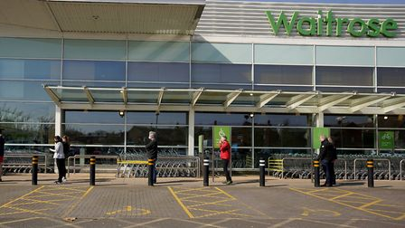 People observe social distancing while queuing at Waitrose supermarket. Picture: Morgan Harlow/PA Wi