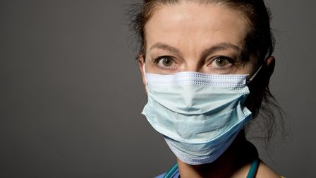 Female nurse/doctor wearing a surgical mask against a dark background. NHS. Picture: Getty Images/iS