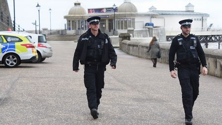 Cromer police Pc Joey Mazzetti, left, and PC Cameron Askew, patrol the promenade checking that peopl