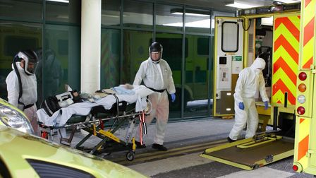 Doctor Rishi Rallan (left) and Critical Care Paramedic Tim Daniels (right) carefully move the patien