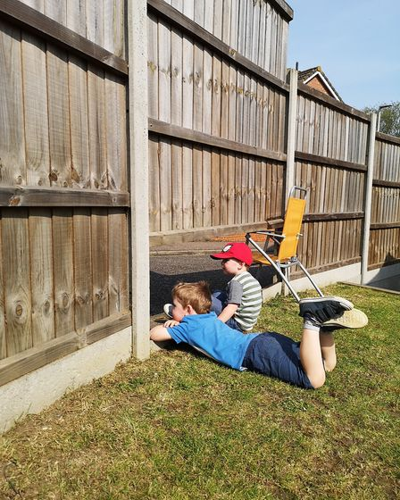 Henry (5) and George (3) chatting to their friend across the road from under the garden fence in Sca