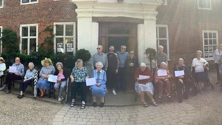"""Residents at Aylsham Manor on Easter Sunday all holding up a piece of paper which reads """"Happy Easte"""