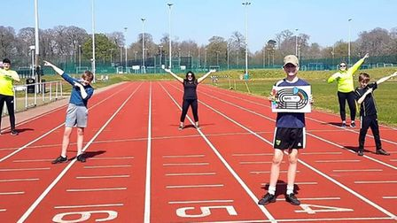 Children holding up the colouring sheet to celebrate the NHS on the Sportspark's athletics track (Cr