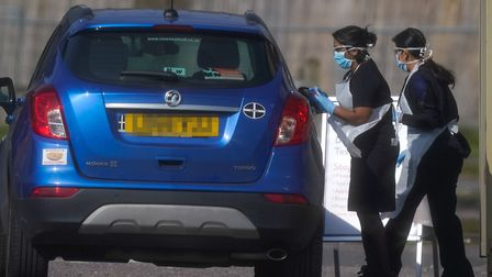 An NHS worker being tested for coronavirus at a temporary drive through testing station at Chessingt