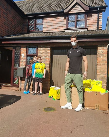 Norwich City defender Christoph Zimmermann poses for a socially distanced picture with a family of f
