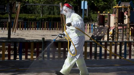 A municipal worker disinfects the outside of a children's play area in Madrid, Spain. Photo: AP/Paul