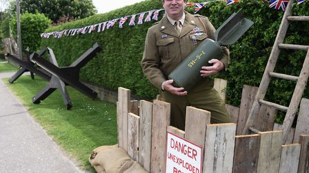 Mark Bailey at his home in Attleborough, with his tribute to VE Day, which includes an unexploded bo