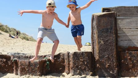 Fletcher Herod, seven, leaps about as he enjoys the beach at Waxham with his brother Charlie, four,