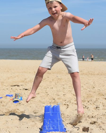 Fletcher Herod, seven, leaps about as he enjoys the beach at Waxham in the hot weather. Picture: DEN