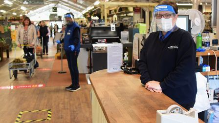 Amanda Middlebrook, retail assistant, wearing a face mask and a shield on the tills, with Clinton Wr