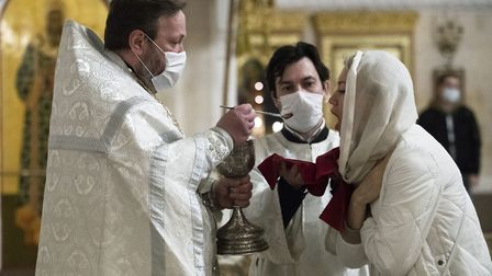 An orthodox priest wearing a face mask to protect against coronavirus distributes Holy Communion dur