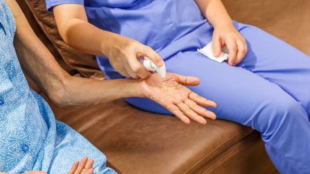 Elderly woman applying hand sanitizer gel from caregiver to helping protect from coronavirus covid-1