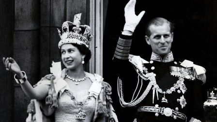 The Duke of Edinburgh with Queen Elizabeth II waving from the balcony to the crowds around the gates