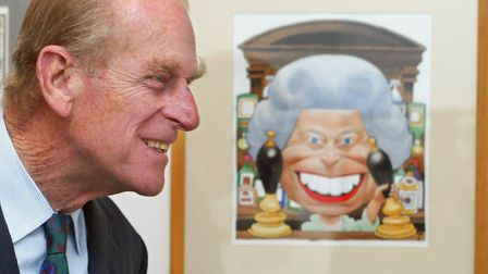 The Duke of Edinburgh looking at a cartoon of Queen Elizabeth II drawn by Trogg for the Golden Jubil