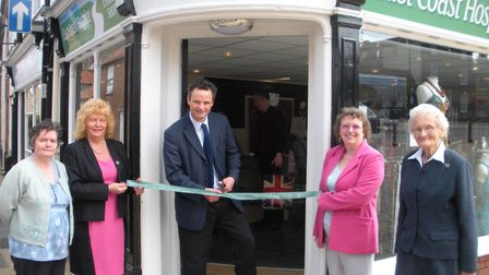 Waveney MP Peter Aldous cuts the tape to open the East Coast Hospice Shop at Beccles watched by hosp