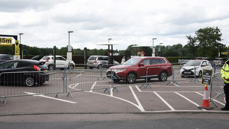 Cars make their way round a fenced queuing area as Brundall Mcdonalds opens the drive through after