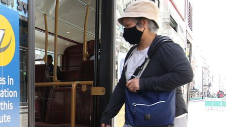 A person wearing a face mask boards a bus on Piccadilly, London, following the introduction of meas
