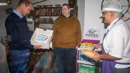 The Duke of Cambridge is presented with a birthday cake by shop owner Paul Brandon (right) during a