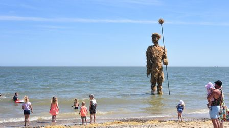 Children paddle in the sea along with the straw 'Pakefield Man' at Lowestoft's First Light Festival.