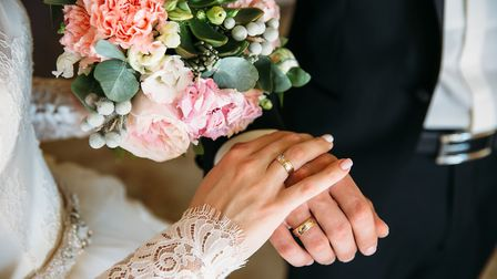 groom and bride are holding hands at wedding day. Picture: Getty Images/iStockphoto