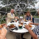 Diners enjoy a meal inside one of the outdoor dining pods which have been installed for social dista