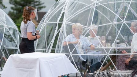 A waitress takes orders from the outdoor dining pods which have been installed for social distancing