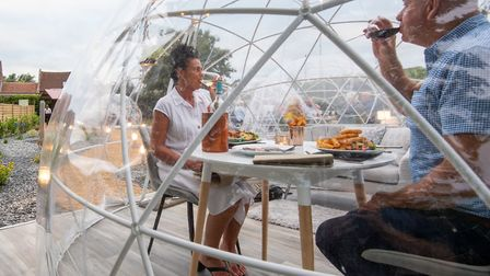 Sally and David Clayton enjoy a meal in one of the outdoor dining pods. Photo: Joe Giddens/PA Wire
