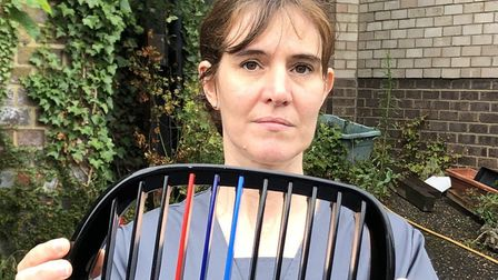 NHS worker Nicola Gibson holding up a grill she believes came from the car which crashed into hers .