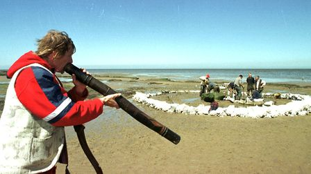 Buster Nolan plays his didgeridoo as the archaeologists continue to excavate the sandbagged site on