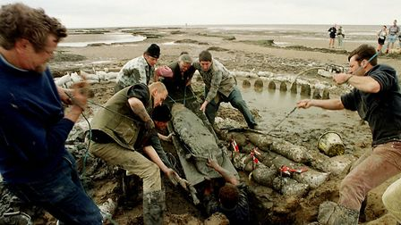 Archaeologists haul a timber out of the beach at Holme Picture: John Hocknell