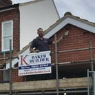 Builder Kevin Baker points to a newly-installed swift box on a brick garage gable in north Norwich.