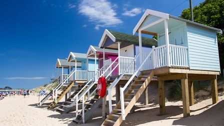 The wide, sand beach at Wells, with its colourful huts and wooded hinterland, is a popular day trip