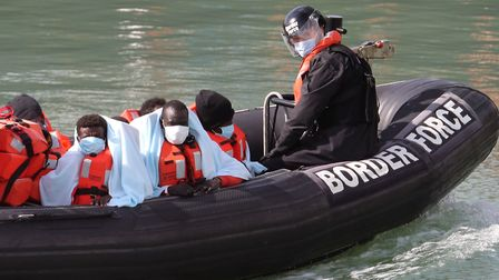 A group of people thought to be migrants are brought into Dover, Kent, by Border Force officers. Pic