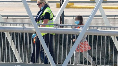 A young girl is escorted by a Border Force officer as groups of people thought to be migrants are br