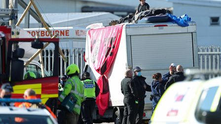 Police and fire service personnel gather around a pair of protesters on top of a van used to block t