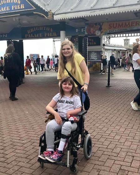Angelina Mills, now 11, seated, and Caity Downs, now 19, on Brighton Pier in August 2018. Picture: S