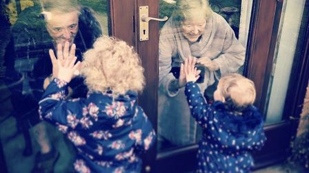 Ray and Theresa Cossey putting their hands up to glass doors to touch the fingers of their great gra