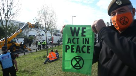 A protester holds up an Extinction Rebellion banner, behind him emergency services use a cherry pick